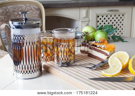 french press, cup of tea and sponge cake with orange, in the interior of Provence