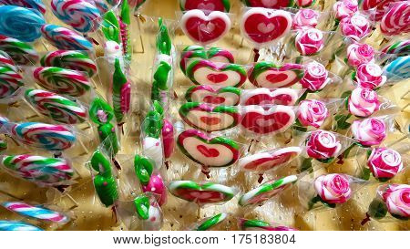 Striped lollipop and multicolored smarties and background