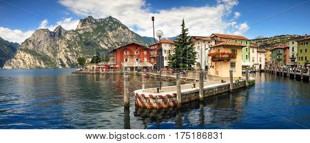 Beautiful italian village town Torbole on lakefront of Lake Garda with colorful houses in summer.