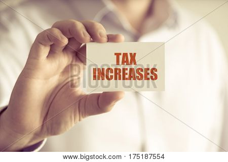 Businessman Holding Tax Increases Message Card