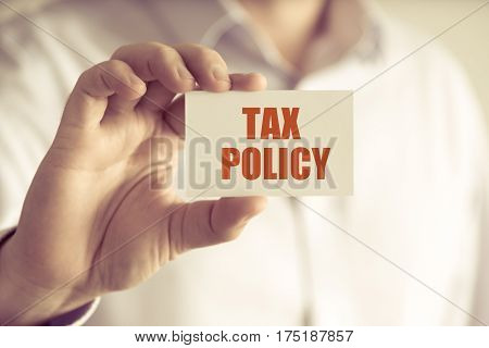 Businessman Holding Tax Policy Message Card