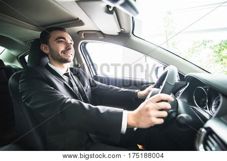 young businessman in his car. Driver of luxuty car. Handsome man drive car inside view