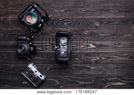 Retro and modern digital camera with virtual reality glasses on dark wooden table