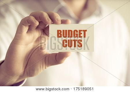 Businessman Holding Budget Cuts Message Card