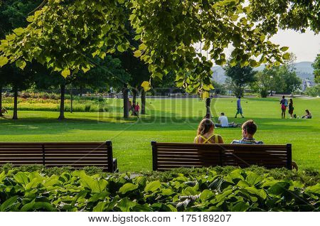 Ottawa, Canada - July 24, 2014: A couple relaxes on a bench framed by trees in Major's Hill Park in Ottawa, Canada.