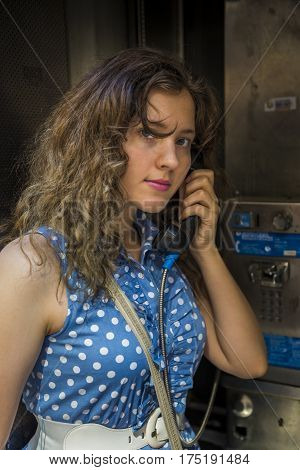 Young woman calling in phone booth in city