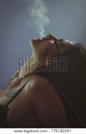 Smokers, Brunette woman with smoke coming out of her lips, concept smoker and tobacco