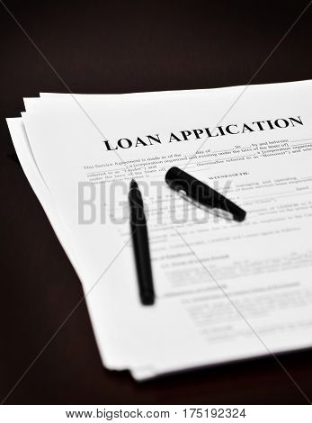 Document loan or contract on a desk with a black pen