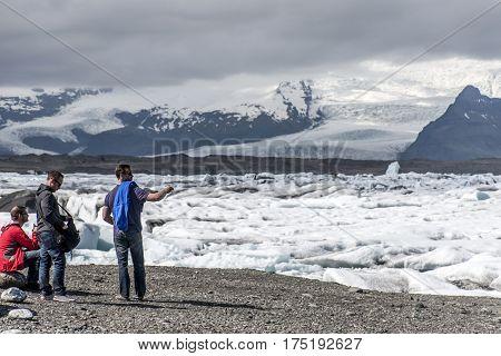 Iceland men standing at glacier lake Jokulsarlon glacial lagoon nature with snow landscape Vatnajokull