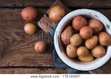 Raw potatoes in a white bowl on a napkin copy spase horizontal