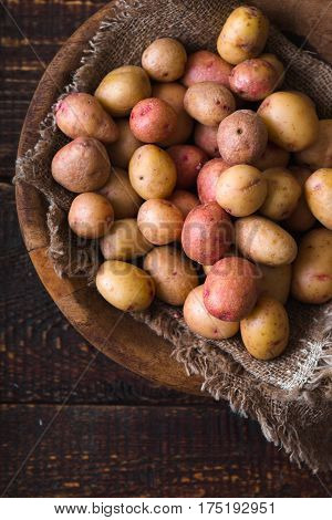 Raw potatoes red and white in a wooden bowl vertical