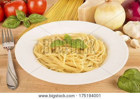 Spaghetti pasta bowl on wooden table. Ingredients in background.