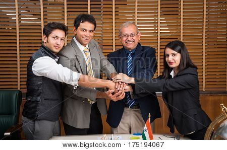 Concept of teamwork: Close-Up of hands, Indian business team showing unity with putting their hands together with smiling faces