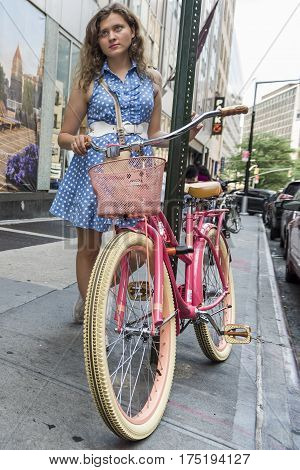 Retro styled young woman with powder blue dress and pink bicycle on New York City street