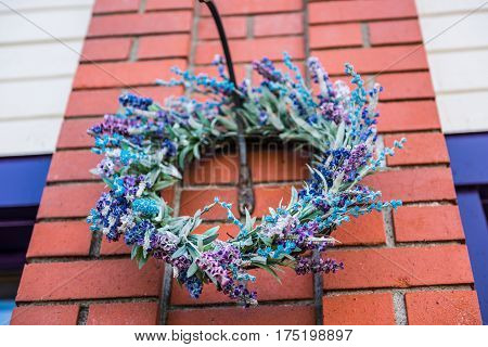 Closeup of woven purple lavender wreath hanging on brick wall