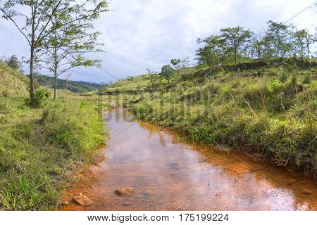 Quiet stream with copper color sediment in green pastures of Chiapas Mexico on the trail to El Chichonal volcano