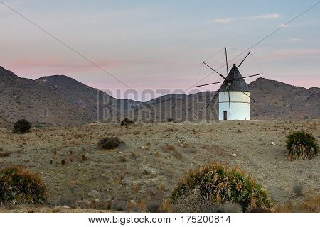 Windmill in Cabo de Gata National Park. Traditional windmill in stone landscape with mountains in the background