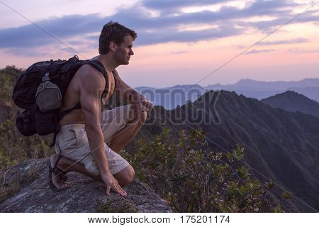 Muscular shirtless man with heavy backpack kneeling on rock overlooking scenic mountain landscape at sunset
