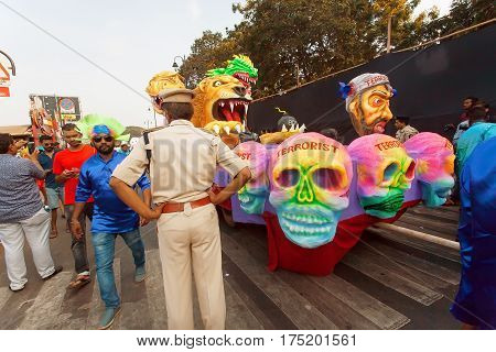 PANAJI, INDIA - FEB 25, 2017: Policeman accompanies procession with figures of defeated terrorists during the traditional Goa carnival on February 25, 2017. Carnaval is celebrated in Goa since 18th century