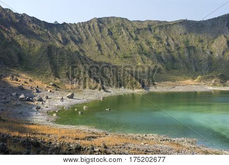 Sulfuric green lake and rugged interior of crater in El Chichonal volcano in Chiapas Mexico on sunny day