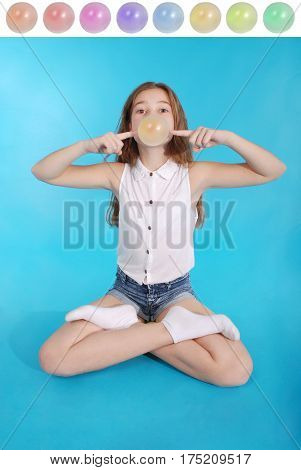 Young girl making a big bubble with a chewing gum isolated on blue. Many varieties of gum color for your projects