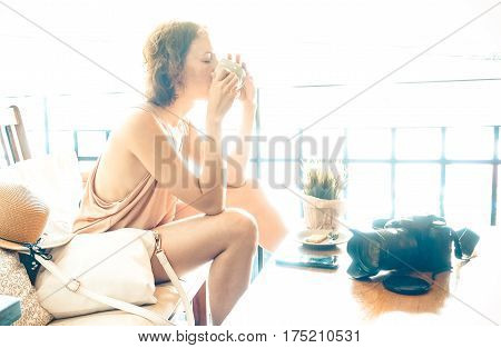 Portrait of young woman drinking cappuccino on relax travel moment - Pretty girl emotional absorbed at coffee bar with dslr photocamera - Inspiration life concept on bright desaturated vintage filter