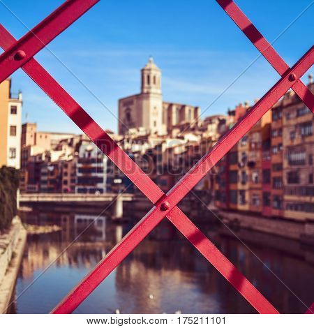 a view of Girona, in Spain, the Onyar River and the Old Town of the city, highlighting the Cathedral on the right, seen through the structure of the characteristic red bridge built by Eiffel