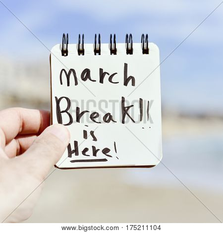 closeup of a the hand of a young caucasian man holding a notepad with the text spring break is here written in it, in front of a beach