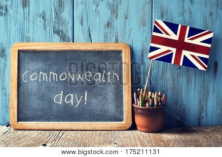 a wooden-framed chalkboard with the text commonwealth day written in it and the Union Flag in a pot of pencils, against a blue rustic wooden background