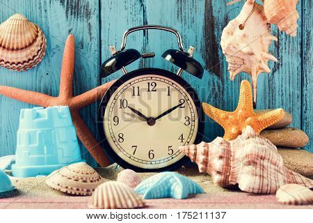 an alarm clock being adjusted forward one hour at the beginning of the summer time, many conches and starfishes, and a beach pail, on a pile of sand, against a bright blue rustic wooden background