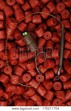 Fishing bait with hook on red pre-drilled halibut pellets for carp fishing background