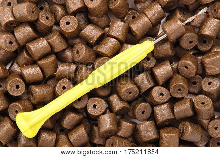 Yellow stinger needle on brown pre-drilled halibut pellets for carp fishing background