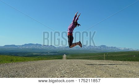 Woman jumping in the air on an empty and unsealed dempster highway