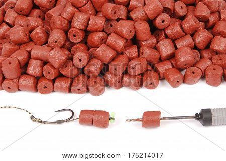 Fishing bait with hook and red pre-drilled halibut pellets for carp fishing isolated on white background with soft shadow