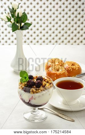 Delicious and healthy breakfast of granola buns brioche honey and black tea on a light background. Soft focus.