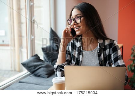 Picture of amazing young caucasian woman wearing glasses sitting indoors using laptop computer while talking by phone and drinking coffee. Coworking concept.