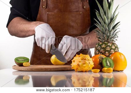 A cut lemon on a cutting board with knife.