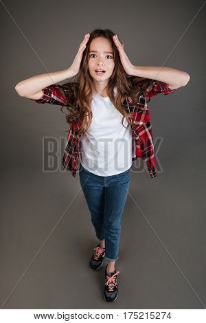 Top view of scared terrified young woman standing and screaming over grey background