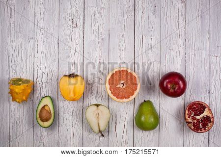 Halves of ripe fresh fruits on a wooden background. Checkerboard pattern