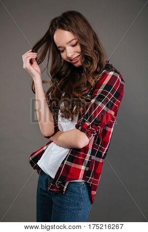 Cute shy young woman in plaid shirt and jeans standing and touching her curly hair over grey background