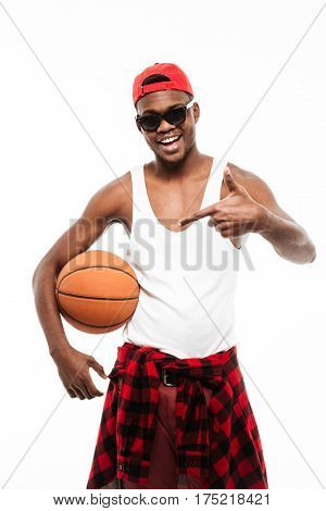 Happy african young man holding basketball ball and pointing away over white background