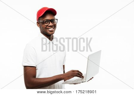 Image of happy young african man wearing cap isolated over white background using laptop computer. Looking at camera.