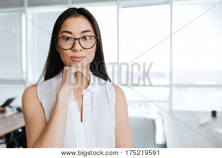 Portrait of beautiful asian young businesswoman in glasses standing in office