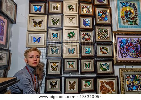 Moscow, Russia - February 25, 2017: A blonde woman with short hair on a stand background with dried insects for interior decoration waiting for buyers