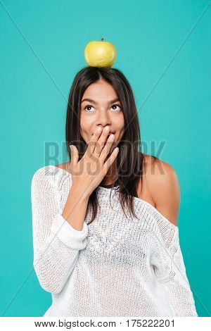 Cute playful young woman with apple on her head standing and covering mouth by hand over blue background