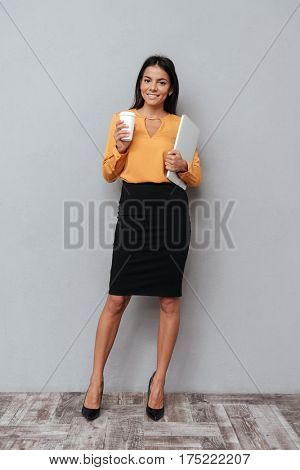 Full length portrait of a smiling young business woman standing with laptop and cup of coffee isolated over gray background