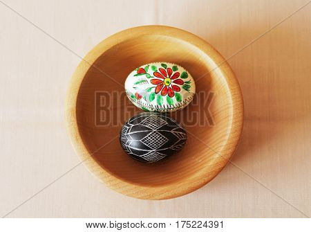two painted Easter eggs in the wooden bowl