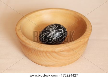 black Easter egg with abstract pattern in the wooden bowl