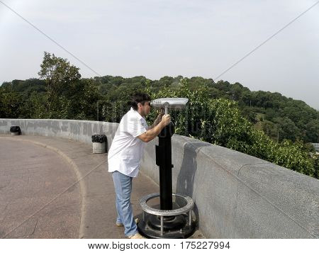 A man looks at the stationary binoculars.