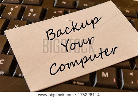 Backup your computer text concept over dark computer keyboard background